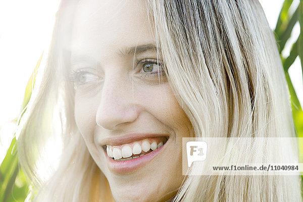 Junge Frau lächelt in Gedanken im Freien