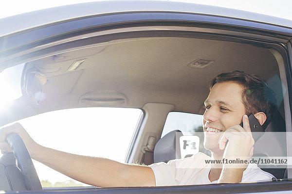 Mann beim Telefonieren während der Fahrt