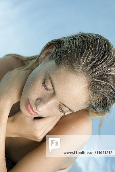 Frau entspannt im Pool mit geschlossenen Augen