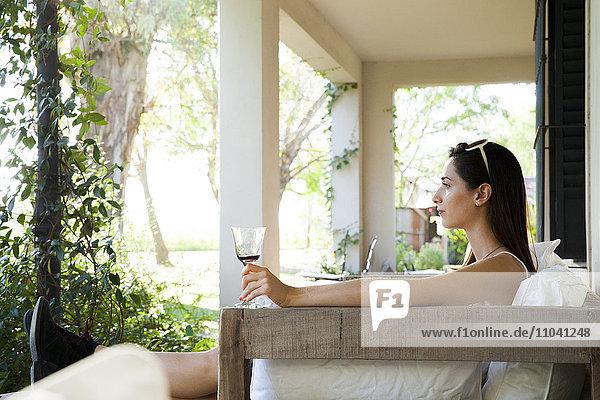 Frau entspannt auf der Veranda bei einem Glas Wein