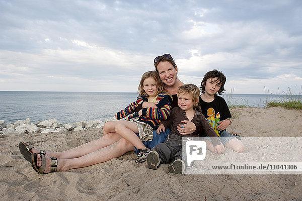 Mutter und Kinder sitzen zusammen am Strand  Portrait