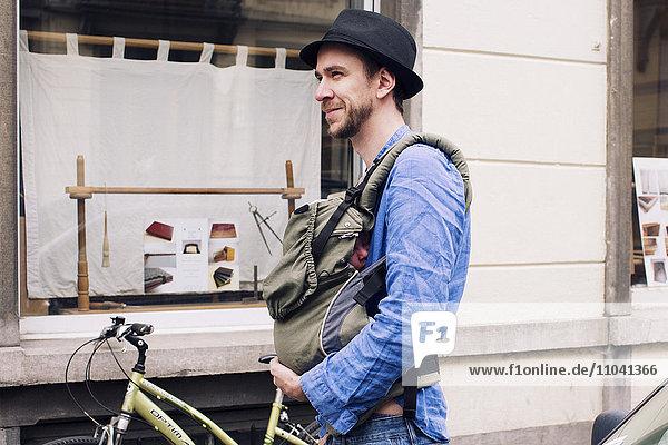 Mann unterwegs in der Stadt mit Baby im Gepäckträger