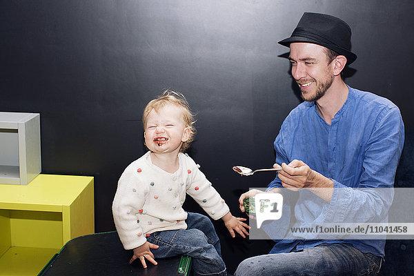 Vater füttert Kleinkindereis Vater füttert Kleinkindereis