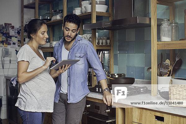 Paar in der Küche mit Blick auf digitales Tablett zusammen