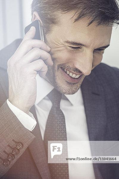 Geschäftsmann im Gespräch am Handy  lächelnd