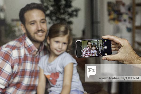 Fotografieren von Vater und Tochter mit dem Smartphone