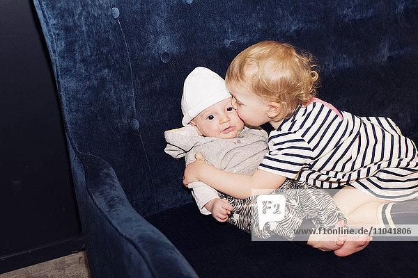 Kleinkind umarmt Geschwisterkind