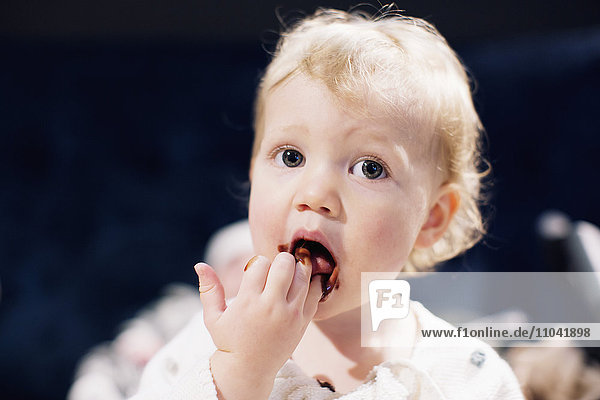 Kleinkind leckt Schokoladensirup von den Fingern Kleinkind leckt Schokoladensirup von den Fingern