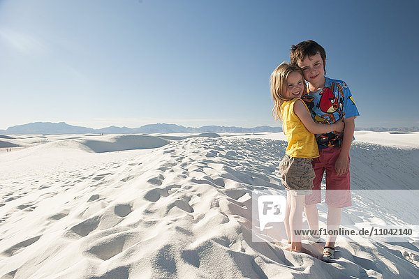 Young siblings standing on dune at White Sands National Monument  New Mexico  USA