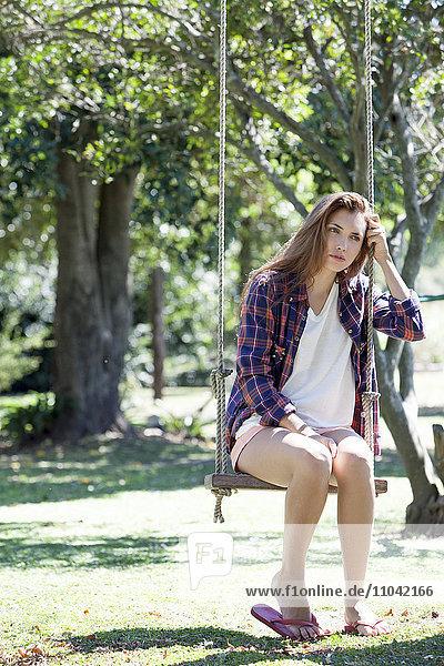 Junge Frau auf Parkschaukel sitzend mit traurigem Gesichtsausdruck
