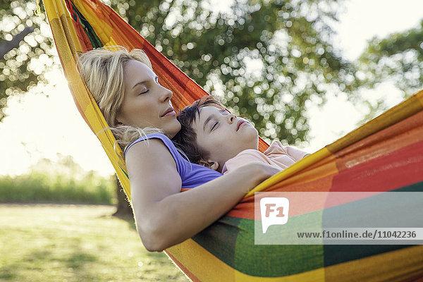 Mutter und Sohn schlafen zusammen in der Hängematte.