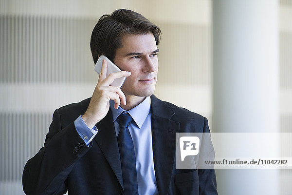Businessman listening to voicemail on cell phone