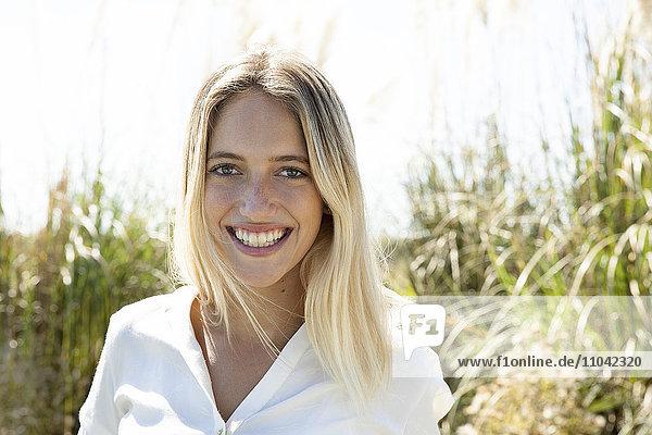 Frau lächelt fröhlich im Freien  Porträt