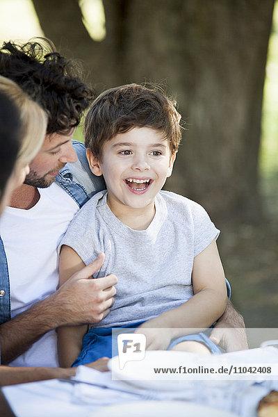 Kleiner Junge auf Vaters Schoß beim Essen im Freien
