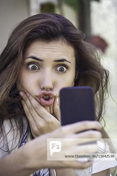 Frau  die Gesichter macht  während sie Selfie nimmt.