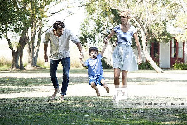 Familie mit einem Kind beim gemeinsamen Spaziergang im Freien