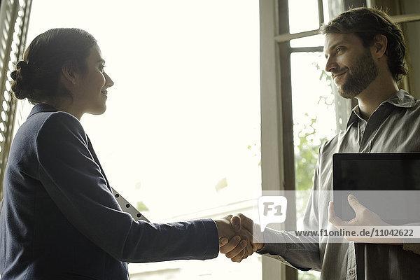 Versicherungsvertreter schüttelt Interessenten die Hand