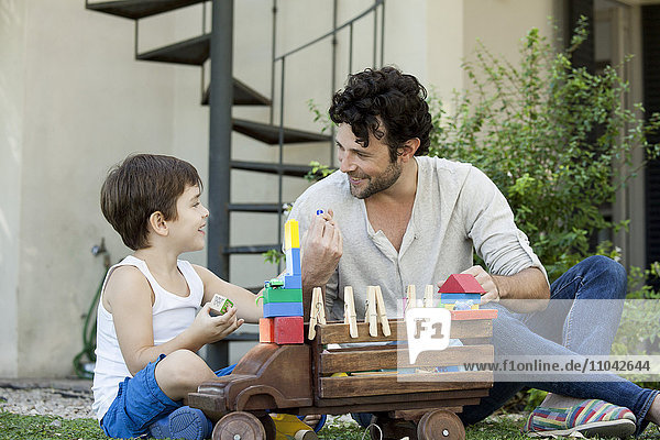 Vater und Sohn spielen gemeinsam mit Spielzeug