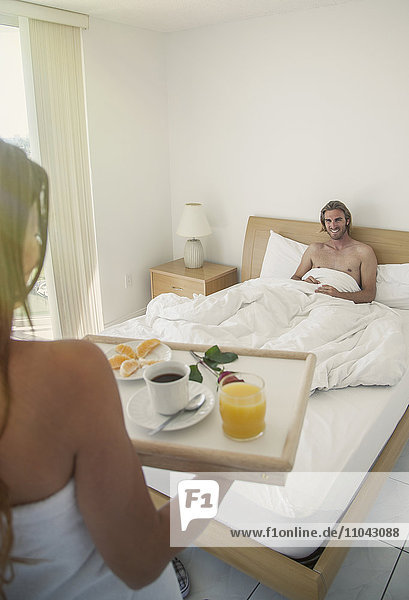 Caucasian woman serving man breakfast in bed