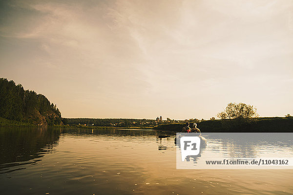 Caucasian family paddling boat on river