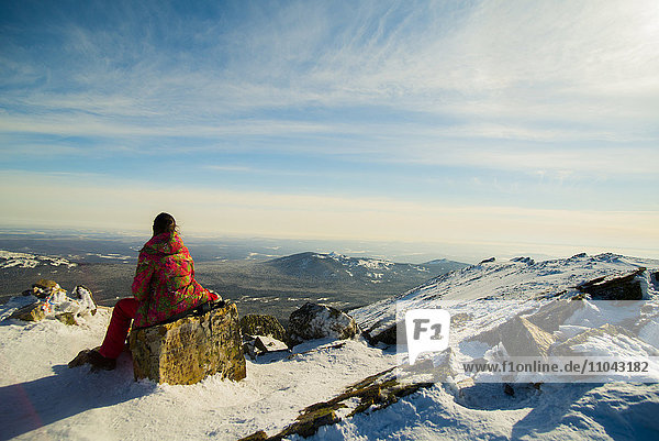 Woman hiker sitting on mountain rock in winter