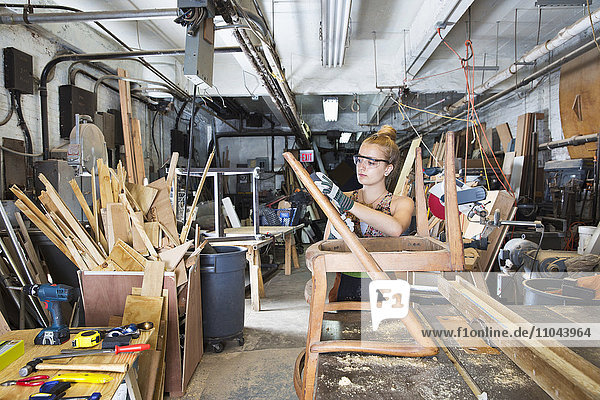 Caucasian woman working on wooden chair in workshop