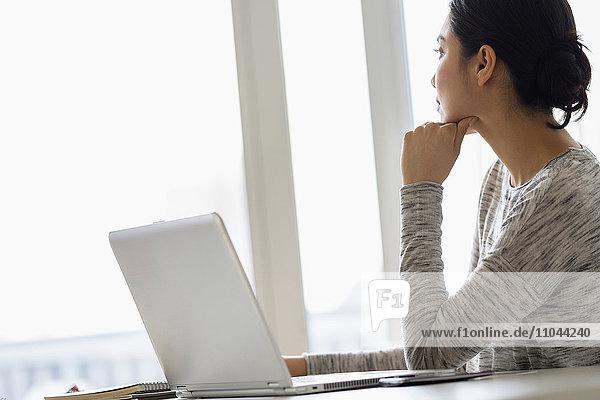 Hispanic woman sitting at laptop