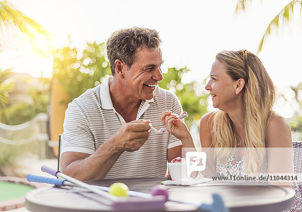 Caucasian couple eating ice cream at outdoor table