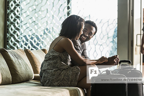 Couple sitting on hotel lobby sofa