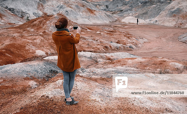 Caucasian woman photographing rock formations