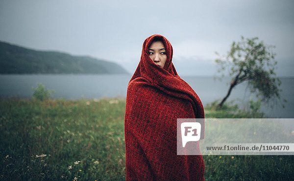 Caucasian woman wrapped in blanket in rural field