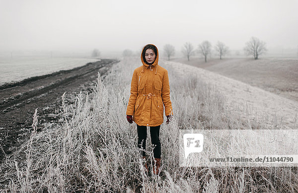 Caucasian woman standing in snowy field