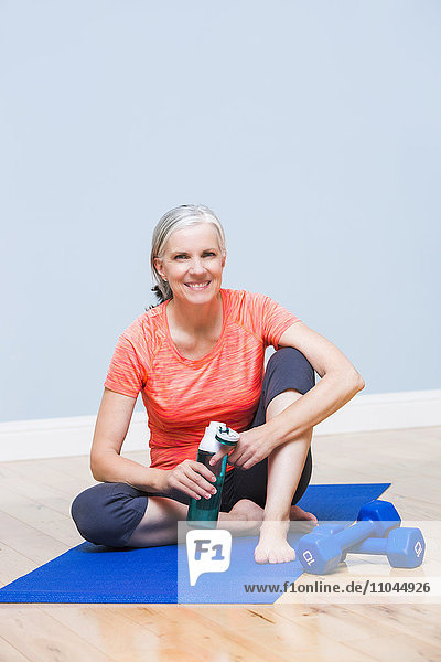 Caucasian woman drinking water on yoga mat