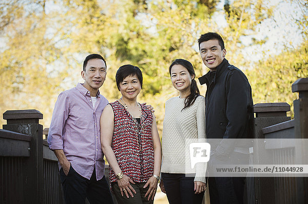 Chinese family smiling outdoors