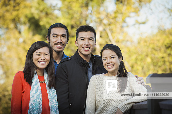 Adult Chinese siblings smiling outdoors