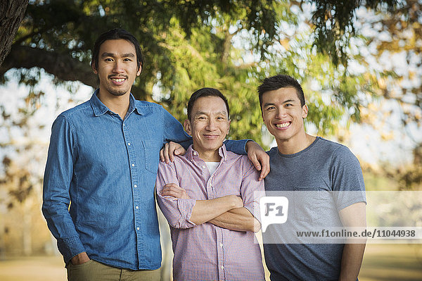 Chinese father and sons smiling outdoors