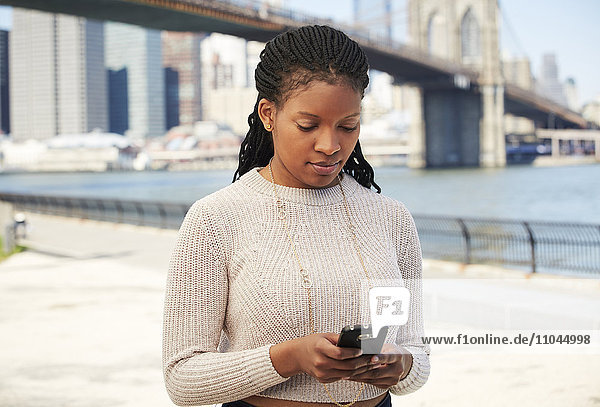 Black woman using cell phone at waterfront