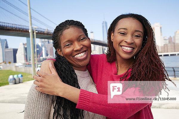 Black women hugging at waterfront