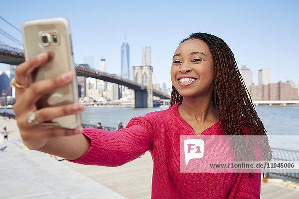 Black woman taking selfie at waterfront
