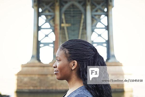 Profile of smiling Black woman at bridge