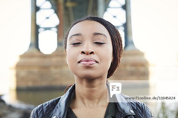 Black woman thinking with eyes closed at bridge