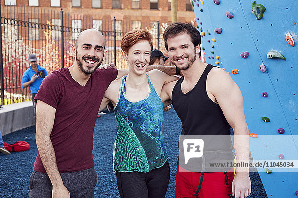 Smiling friends posing at outdoor climbing wall