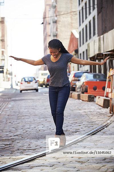 Black woman balancing on track in cobblestone city street