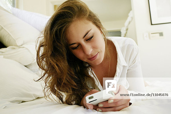 Mixed race woman using cell phone on bed