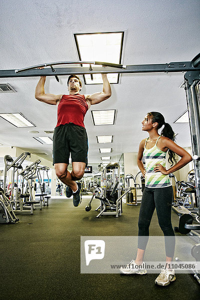 Man working out with trainer in gymnasium