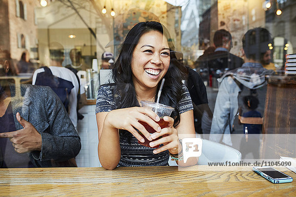 Mixed Race woman smiling in cafe window