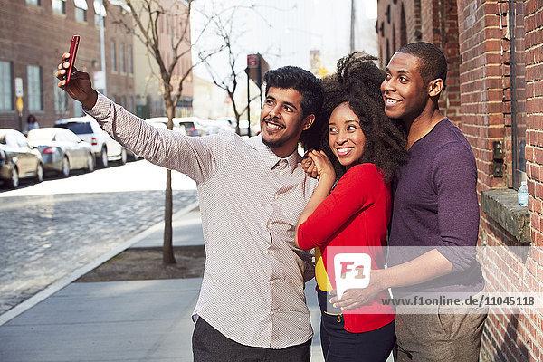 Smiling friends taking selfie on city sidewalk