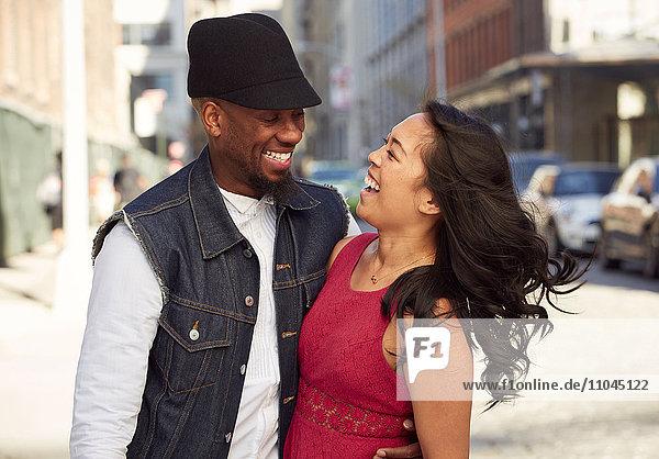 Couple laughing on city sidewalk