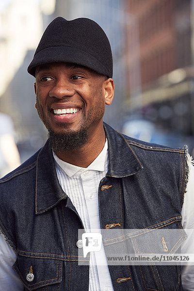 Smiling African American man wearing hat and denim vest
