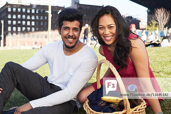 Couple sitting on grass with picnic basket
